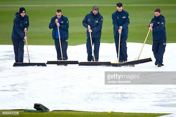 Groundsmen work to dry the field as rain stops play during day two of the Specsavers County Championship Division One match between Hampshire and...