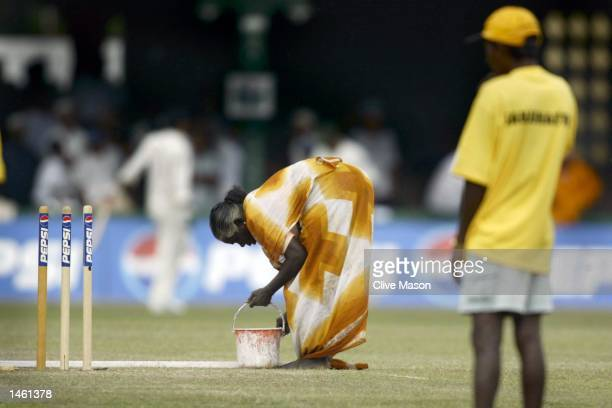 Groundstaff attend to the wicket as rain stops play during the second session of the fourth day of the first test match between Pakistan and...