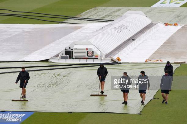 Groundstaff brush water from the covers on the pitch after rain disrupted play on the third day of the first Test cricket match between England and...