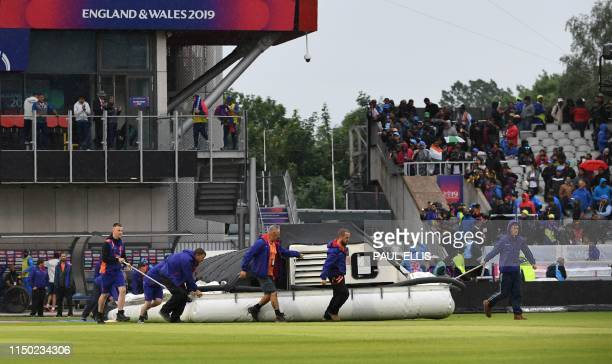 Groundstaff cover the playing area as rain stops play during the 2019 Cricket World Cup group stage match between India and Pakistan at Old Trafford...