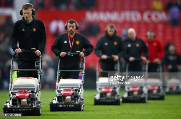 Groundstaff cut the grass after the Premier League match between Manchester United and Liverpool FC at Old Trafford on February 24, 2019 in...