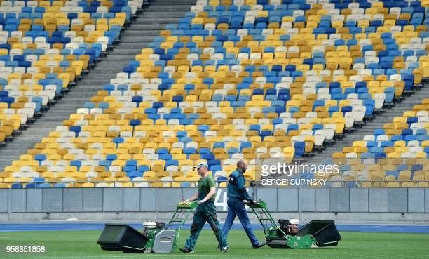 Groundstaff cut the playing surface of The NSC Olimpiyskiy Stadium in Kiev on May 14 ahead of the 2018 UEFA Champions League Final football match...
