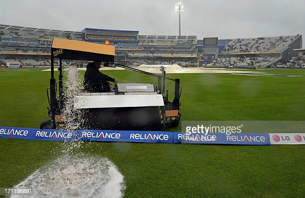 Groundstaff empty rainwater from the Blotter as rain delays the start of play in the 2013 ICC Champions Trophy Final cricket match between England...