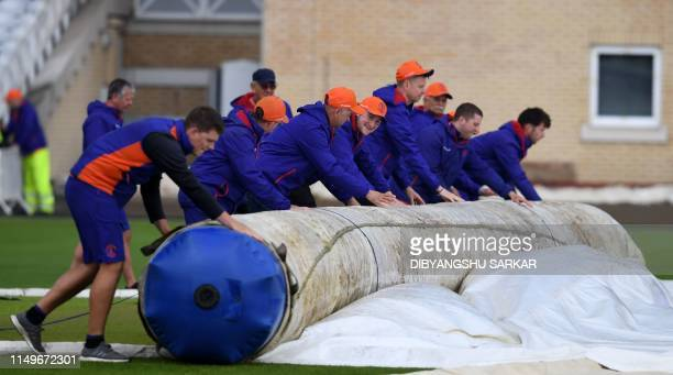 Groundstaff members roll up covers ahead of the 2019 Cricket World Cup group stage match between India and New Zealand at Trent Bridge in Nottingham...