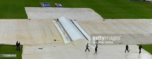 Groundstaff mop up rain during during the 2013 ICC Champions Trophy cricket match between Australia and New Zealand at Edgbaston in Birmingham...