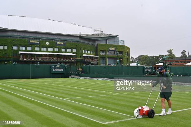 Groundstaff paint the lines a court on the first day of the 2021 Wimbledon Championships at the The All England Tennis Club in Wimbledon, southwest...
