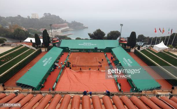 Groundstaff pull covers across the court surface as play is suspended due to rain on day two of the Monte-Carlo ATP 1000 Masters Series tennis...
