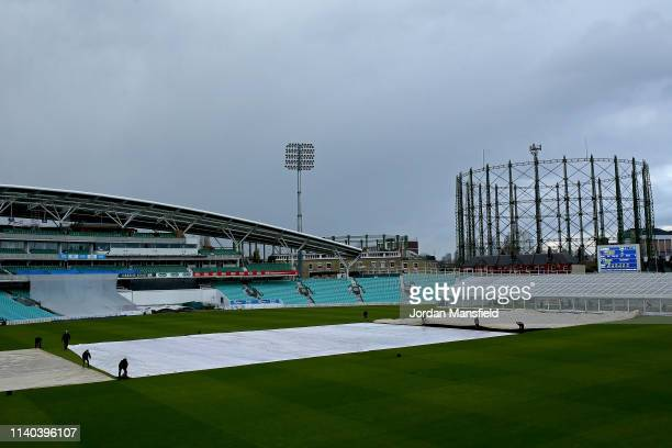 Groundstaff pull the covers on as rain delays play during day one of the English MCC University Match between Surrey and Durham University at The Kia...