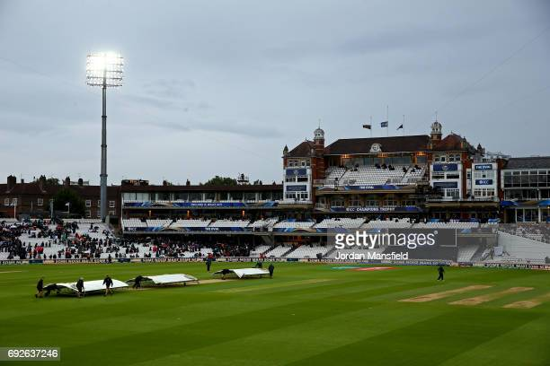 Groundstaff pull the covers on as rain delays play during the ICC Champions Trophy match between Australia and Bangladesh at The Kia Oval on June 5...