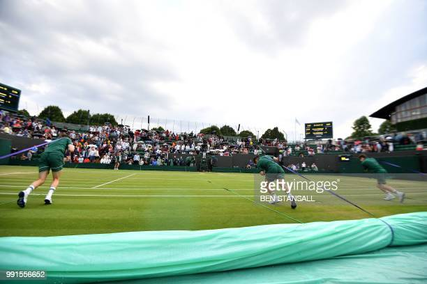 Groundstaff pull the covers over the grass as rain stops play between Switzerland's Stan Wawrinka and Italy's Thomas Fabbiano during their men's...