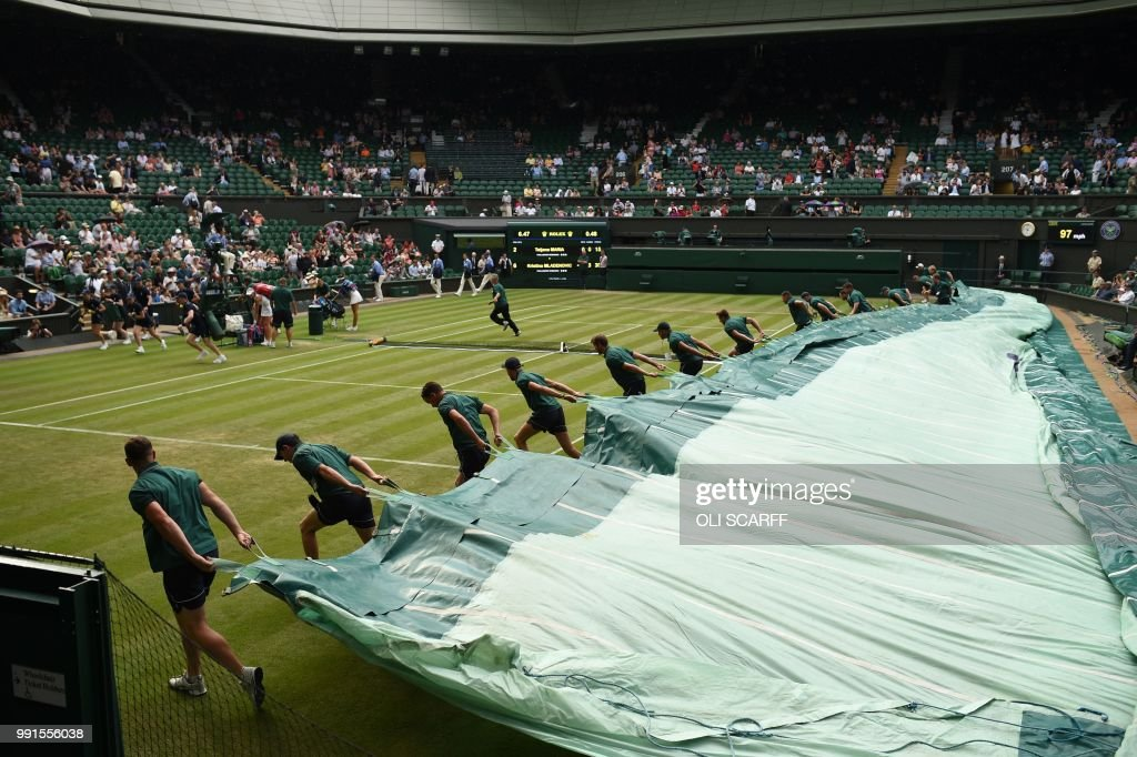 Groundstaff pull the covers over the grass court as rain stops play between Germany's Tatjana Maria and France's Kristina Mladenovic during their women's singles second round match on the third day of the 2018 Wimbledon Championships at The All England Lawn Tennis Club in Wimbledon, southwest London, on July 4, 2018. (Photo by Oli SCARFF / AFP) / RESTRICTED