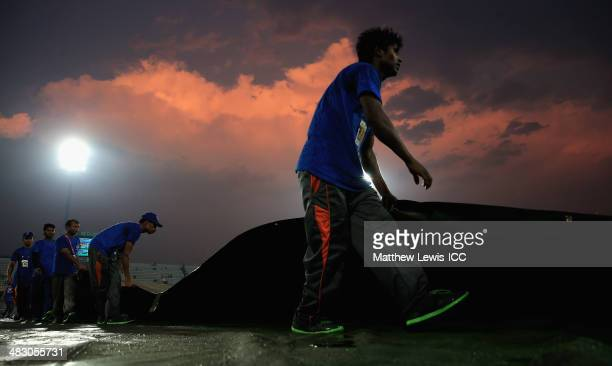 Groundstaff remove the covers after rain delays the start of the ICC World Twenty20 Bangladesh 2014 Final between India and Sri Lanka at ShereBangla...