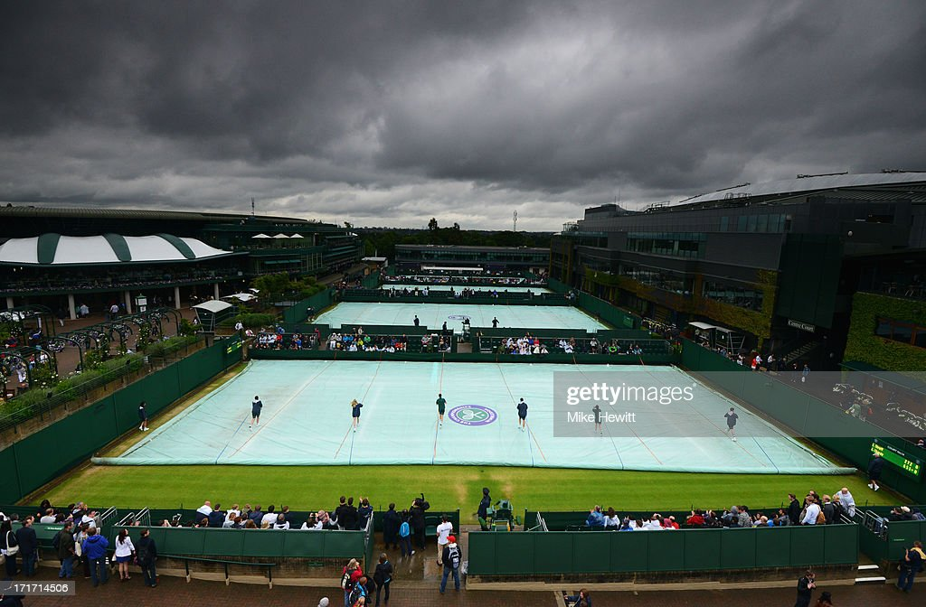 Groundstaff remove the covers from court fourteen on day five of the Wimbledon Lawn Tennis Championships at the All England Lawn Tennis and Croquet Club on June 28, 2013 in London, England.
