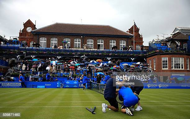 Groundstaff remove the net as rain delays play during day one of the Aegon Championships at Queens Club on June 13 2016 in London England