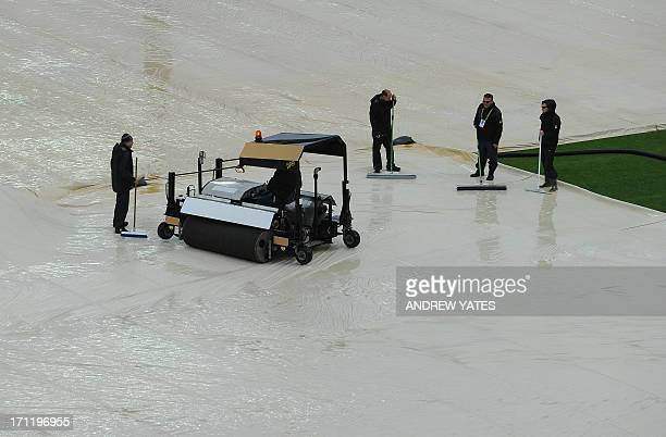 Groundstaff remove water from the the covers with squeegees as rain delays the start of play in the 2013 ICC Champions Trophy Final cricket match...