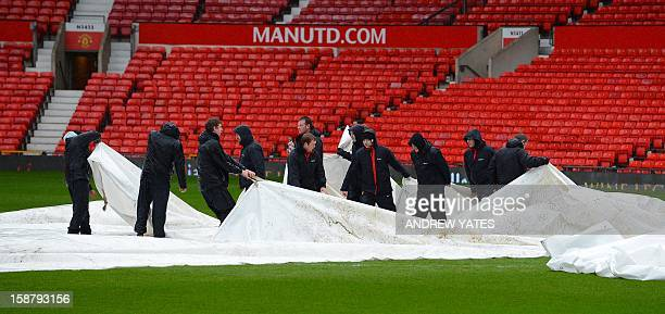 Groundstaff remove waterproof covers from the pitch before the English Premier League football match between Manchester United and West Bromwich...