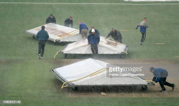 Groundstaff rush to cover the wicket during a sudden downpour in the Benson and Hedges Cup Semi Final between Yorkshire and Essex at Headingley Leeds...