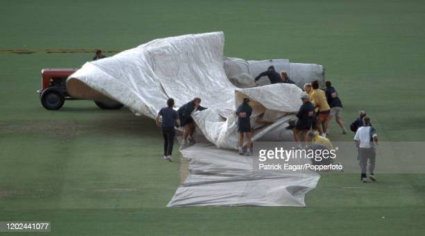 Groundstaff struggle with the covers as a storm stops play early on day one of the 4th Test match between Australia and England at the Adelaide Oval...