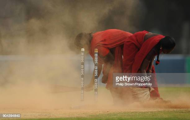Groundstaff sweep the wicket during a break in play following the fall of England's eighth wicket of the 2nd innings of the 1st Test match between...