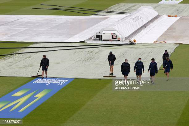 Groundstaff tend to the pitch after rain disrupted play on the third day of the first Test cricket match between England and New Zealand at Lord's...