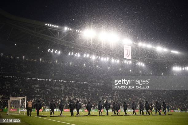 Groundstaff use brooms to sweep snow from the playing surface during the half-time break in the Italian Tim Cup football match between Juventus and...