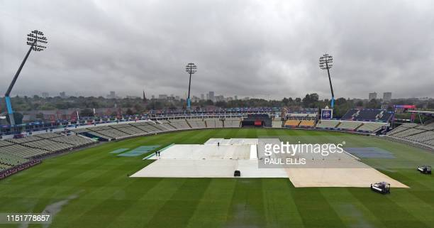 Groundstaff work on a rain soaked pitch at Edgbaston in Birmingham, England on June 25, 2019 on the eve of the ICC World Cup match between Pakistan...