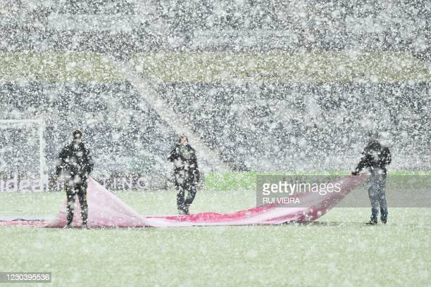Groundstaff work on the pitch as snow falls ahead of the English Premier League football match between West Bromwich Albion and Arsenal at The...