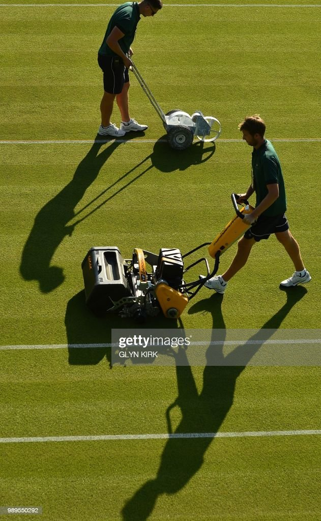 Groundsworkers tend to the grass courts at The All England Tennis Club in Wimbledon, southwest London, on July 2, 2018, on the first day of the 2018 Wimbledon Championships tennis tournament. (Photo by Glyn KIRK / AFP) / RESTRICTED
