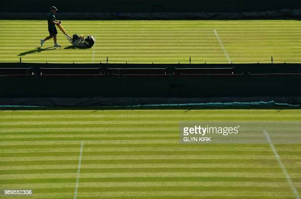 Groundsworkers tend to the grass courts at The All England Tennis Club in Wimbledon, southwest London, on July 2 on the first day of the 2018...