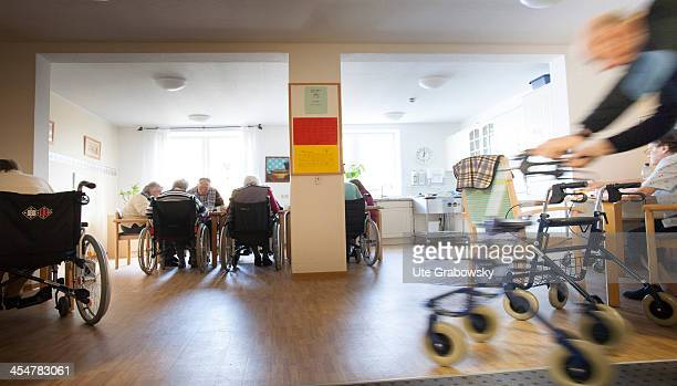 A group 90 year old residents sitting in their wheelchairs having lunch at the table with a blurred image of a walking frame user in the foreground...