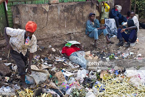 A group a young men and boys sniff glue and hang out in a rubbish site in central Thika Kenya