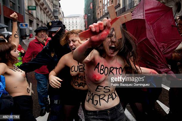 FEMEN group activists with body painting reading 'abortion is sacred' shout slogans and hold a cross as a ProLife demonstration takes place on Alcala...
