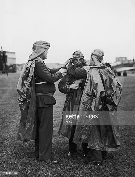 Group Captain R T Leather AFC adjusts the gas mask of an RAF mechanic at Benson Aerodrome during World War II 17th August 1939 Groundstaff and pilots...
