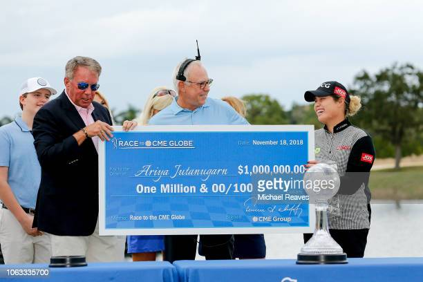 Group Chairman and CEO Terry Duffy presents Ariya Jutanugarn with the Race to the CME Globe check after the final round of the LPGA CME Group Tour...