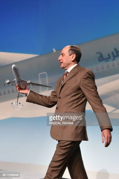 Group Chief Executive of Qatar Airways Akbar Al Baker walks with a model aircraft during a press conference announcing the delivery of the first...