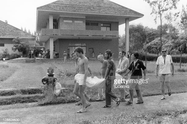 Group coming out of the French Embassy in Phnom Penh carry carefully something on a piece of clothing late April 1975. On New Year's Day 1975,...