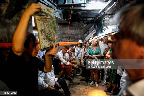 """Group comprising members of the French parliament tours inside an ancient tunnel road called the """"Pilgrims' Road"""" at the City of David archaeological..."""
