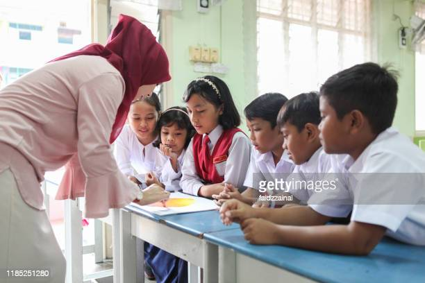 group discussion of school children in a classroom - malaysia stock pictures, royalty-free photos & images