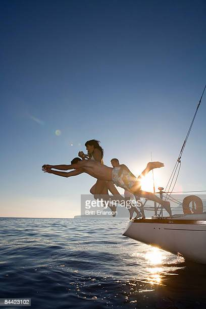 Group dive off back of sailboat