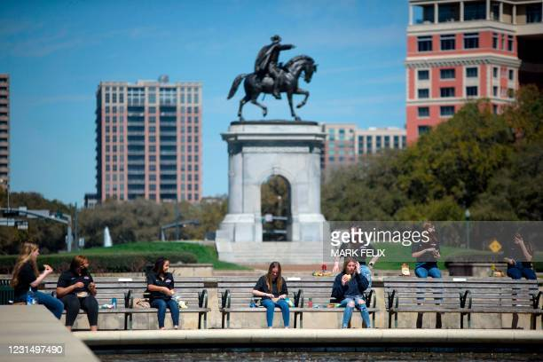 Group eats lunch outside while socially distancing at Hermann Park in Houston, Texas on March 3, 2021. - Texas Governor Greg Abbott announced he is...
