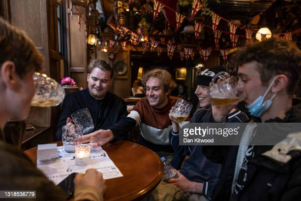 Group enjoy a pint in a Soho pub on May 17, 2021 in London, United Kingdom. From today, covid restrictions on indoor activities and household mixing...