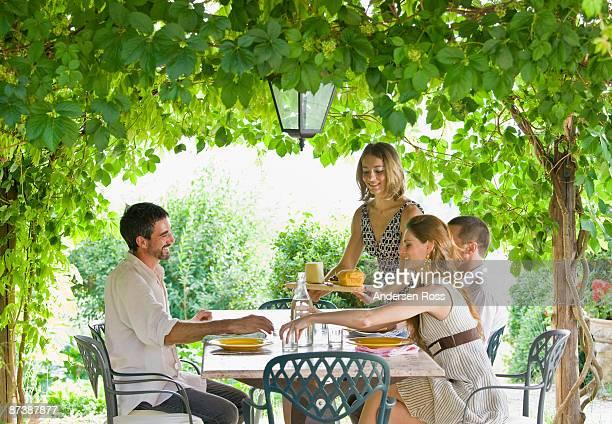 group enjoying meal in garden - pergola photos et images de collection