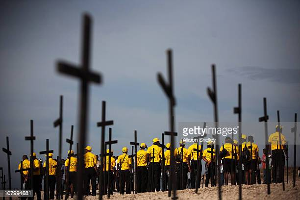 A group gathers in front of crosses set up as a memorial in memory of the tens of thousands killed and buried in the mass grave at Titanyen on...