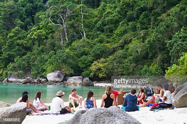A group gathers on a Thai beach.