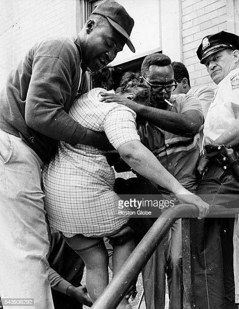 Group helps to lift a young girl on the steps outside of the welfare office at 515 Blue Hill Ave. In Roxbury on June 2, 1967. A group of mothers were...