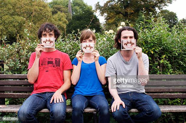 group hiding behind fake paper masks smiling