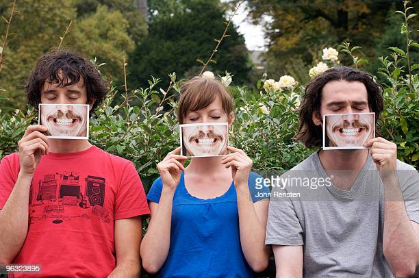 group hiding behind fake paper masks smiling  - teeth stock pictures, royalty-free photos & images