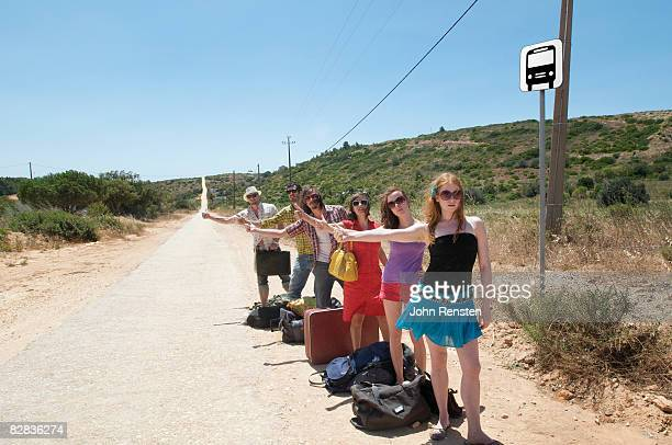 group hitch hiking thumbing a lift on deserted roa