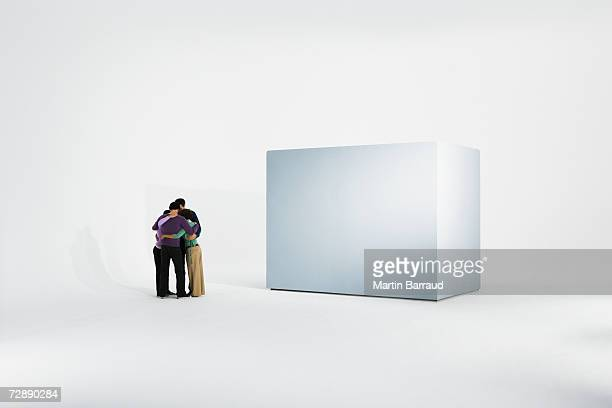 Group huddle beside empty giant box