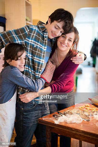 Group hug for mother and sons over pastry making table.